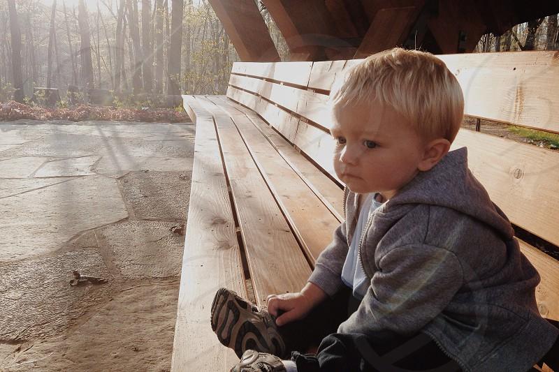 boy in grey hoodie sitting on bench photo