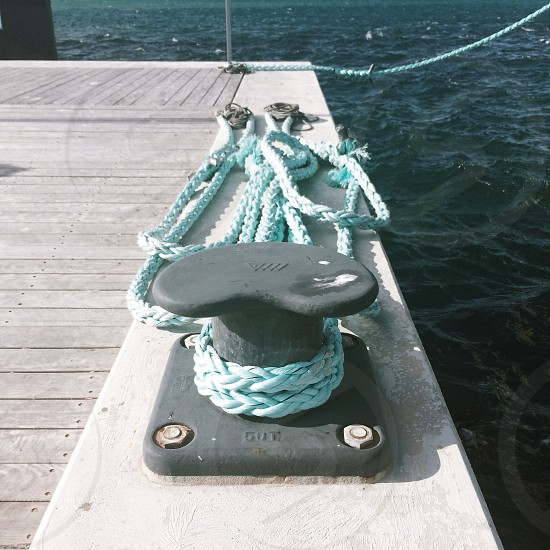 blue rope tied on black dock cleats during daytime photo