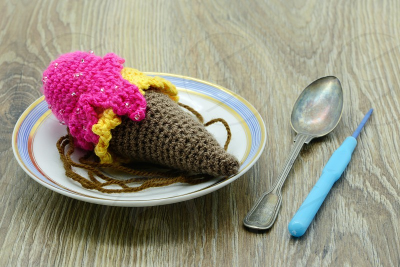 crochet ice cream cone with on plate with spoon and crochet hook. table background. photo