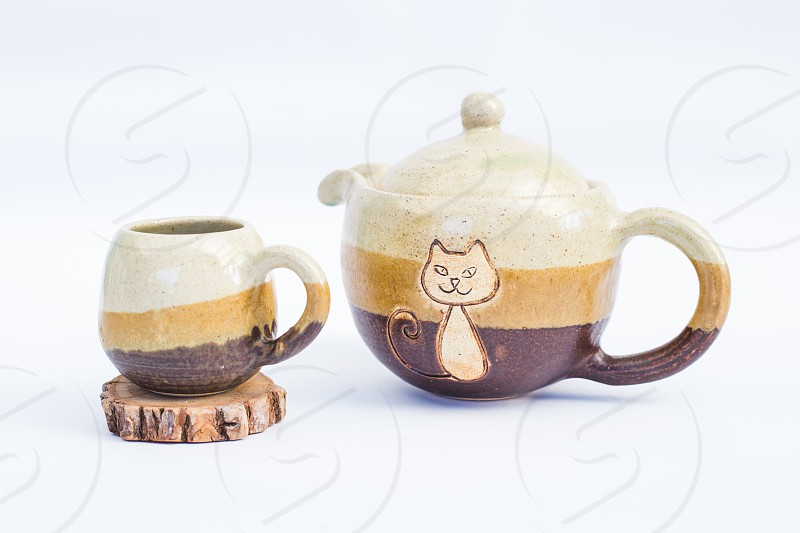 teapot and ceramic stoneware cup with white background photo