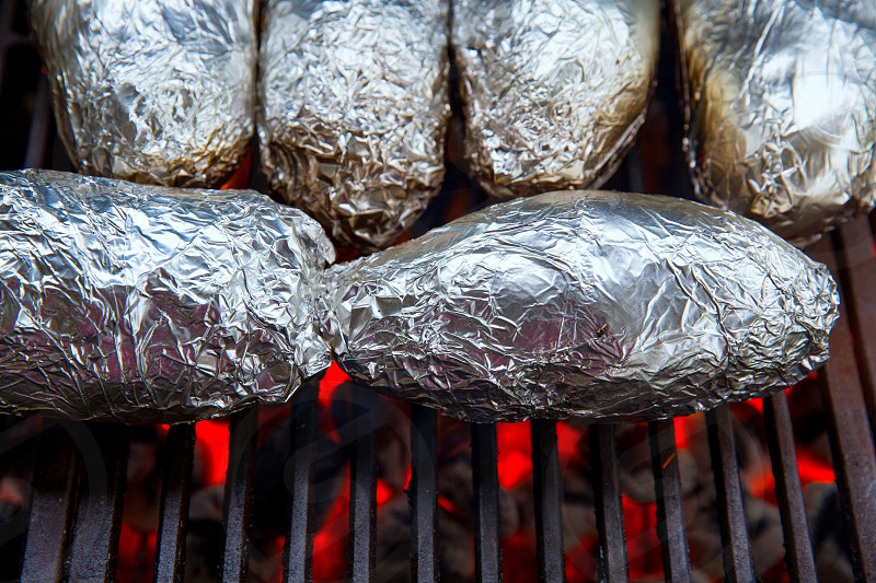 grilled whole potatoes with foil delicious meal and embers photo