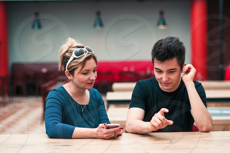 Woman and young man talking together and using mobile phones sitting by a table in cafe photo