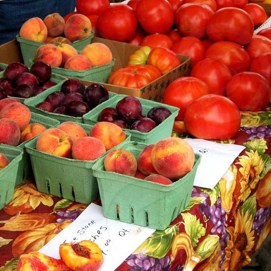 Farmers market table with peaches plums and tomatoes photo