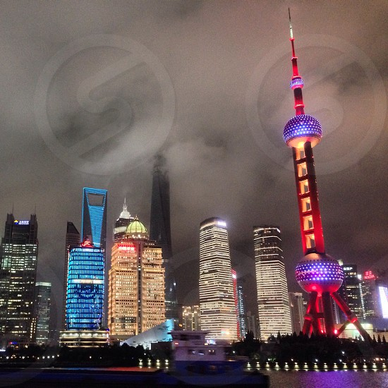 Lit-up Shanghai Pudong cityscape viewed from the Huangpu River on dark stormy evening - with the frame of the new Shanghai Tower rising ominously into the cloudy sky in the background. photo
