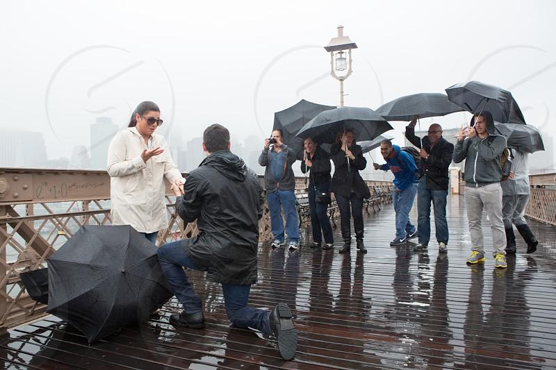 people with umbrellas on a rainy bridge photo