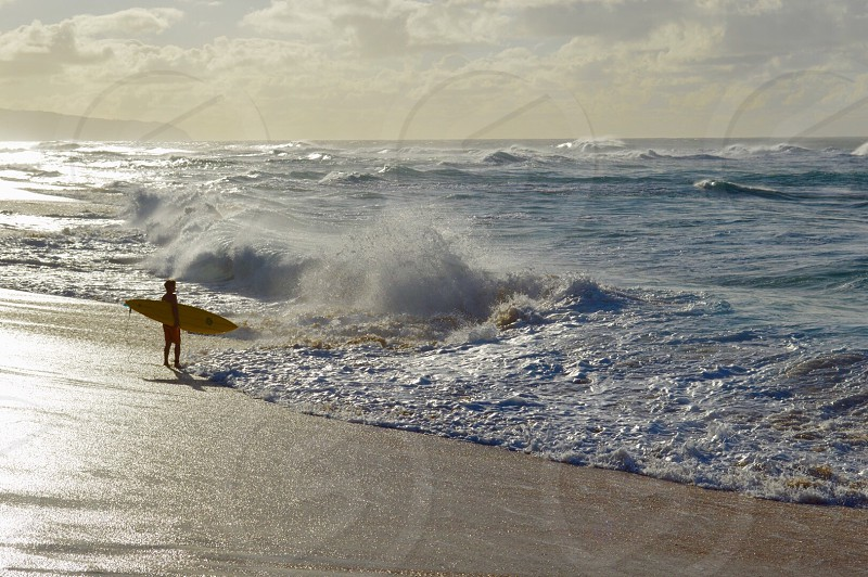 person carrying yellow surfboard in front of blue water waves photo