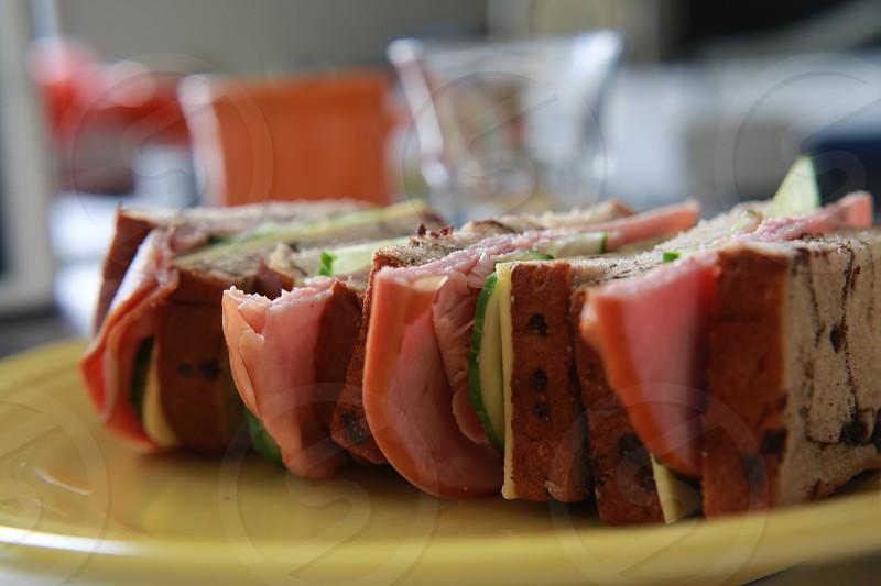 Sandwiches cheese ham cucumber slices bread yellow plate orange mug photo
