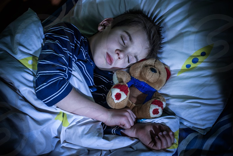 Sleeping child with his toy bear. photo