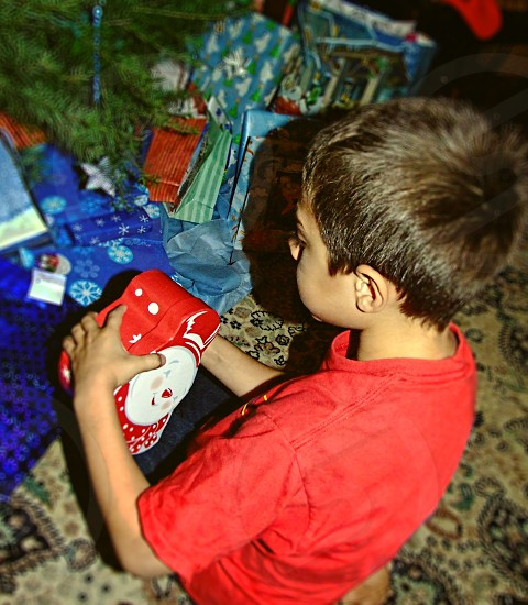 A little boy opens presents on Christmas morning photo