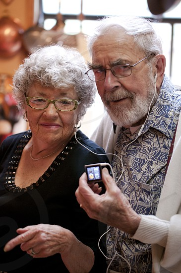 Old couple listening to iPod - sharing earbuds photo