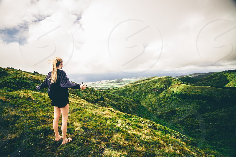woman on top of a grassy hill photo