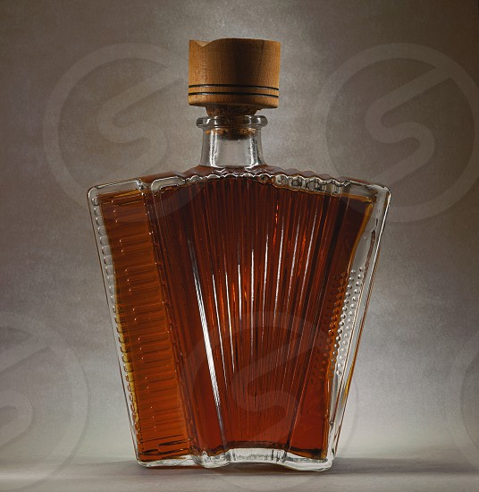 Accordion bottle made of glass as souvenir on gray background.  photo