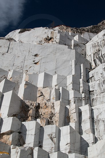 """The hollow channel of Colonnata constitute the more imposing Apuan basins and offer superb views of the """"ravaneti"""" the spectacular accumulation of debris of white marble lying on the sides of the mountains Serrone Maggiore and Spallone the top of which is the basin Gioia: a complex of quarries which offers a unique glance. photo"""