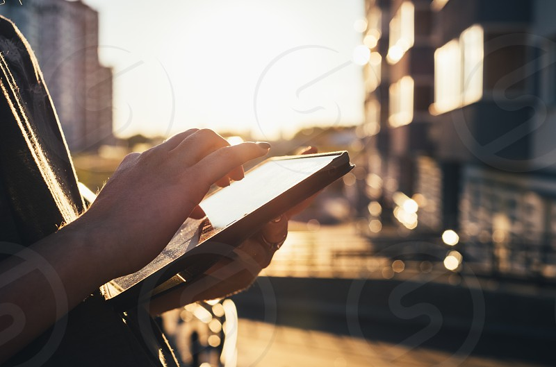woman using tablet at sunset photo