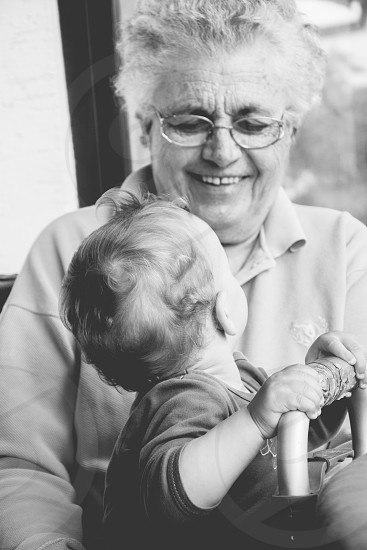 Grandmother smiling while having fun with her youngest grandchild. photo