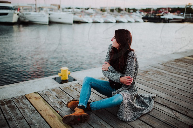 Stylish girl is feeling cold sitting on the pier photo