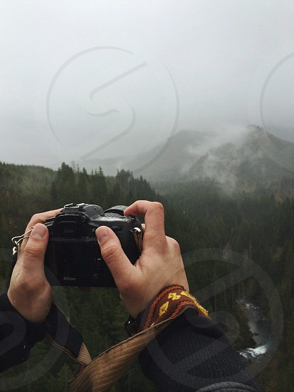 person holding black camera near white snow covered mountains photo