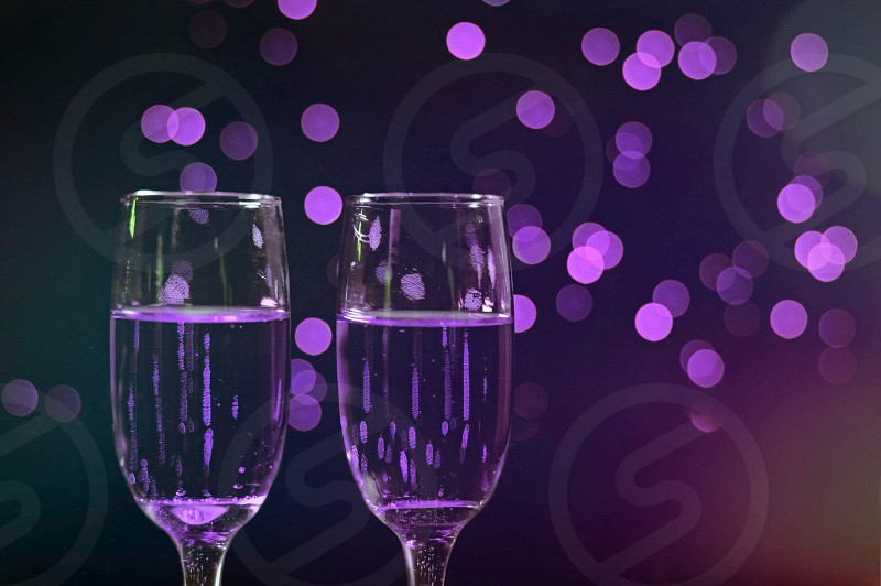 Two glasses of champagne lit up by purple lights and Bokeh. photo