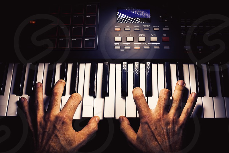 Details of a modern midi keyboard with male hands playing on it.  photo