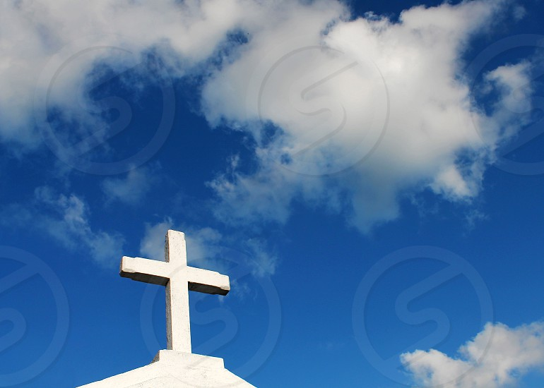 White cross and a sky with white clouds. photo
