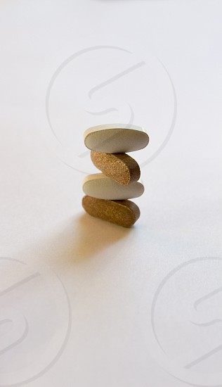 pile of pills white and brown on white background medicine health photo