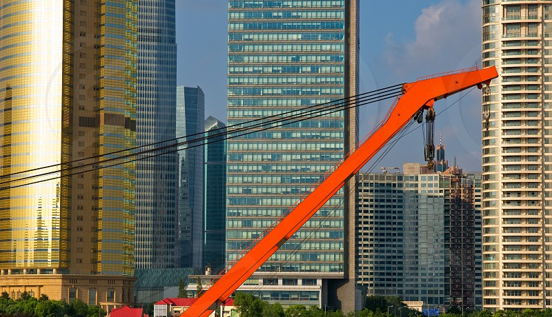 shanghai pudong view from puxi with big red crane boat crossing  huangpu river photo
