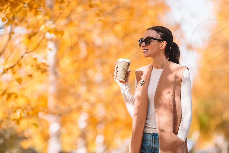 Autumn fall concept - beautiful woman drinking coffee in autumn park under fall foliage. Golden autumn park photo