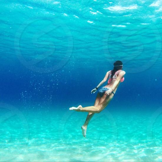 woman wearing bikini swimming in body of water photo