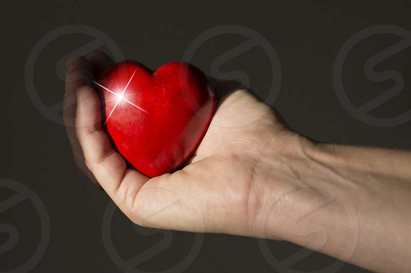 red heart shining in womans hand on dark background photo