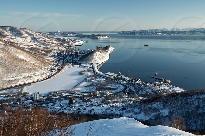 Beautiful winter Kamchatka landscape: top view of the Petropavlovsk-Kamchatsky City Avacha Bay and Pacific Ocean at sunset. Far East Russia Kamchatka Peninsula. (Evening lighting.) photo