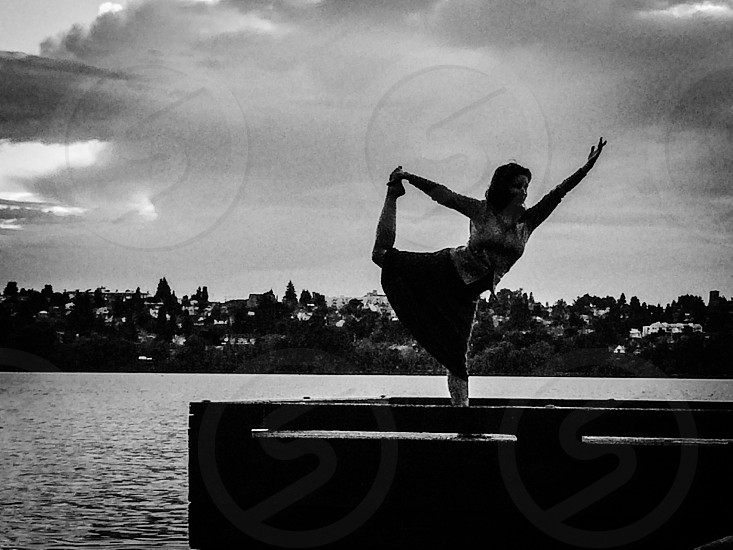 Woman arms up yoga pose on the dock photo