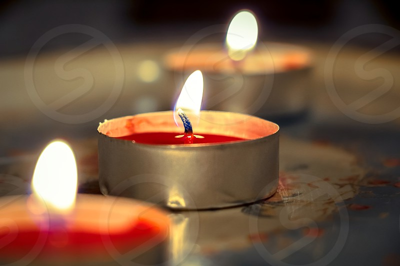 Close up of burning red candles on an old tray.