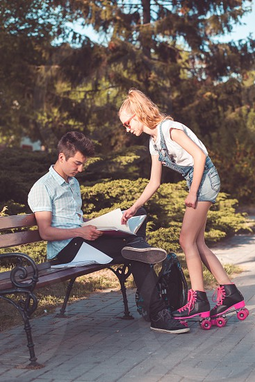 Student boy making the notes learning from books sitting on a bench in a park. Girl relaxing on roller skates. Young boy wearing a blue shirt and dark jeans. Young blondie girl wearing jeans and sunglasses photo
