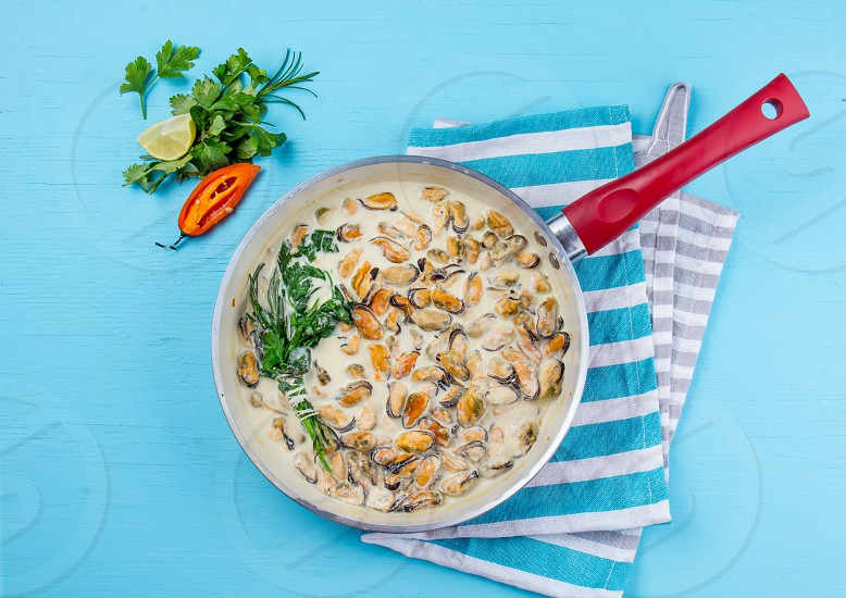 Mussels in milk cream y sauce with aromatic herbs and lemon in red cooking pan. Blue background. photo