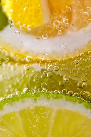 Pieces of citrus fruits of lemon and lime with bubbles in a glass of water. Macro photo of summer drink photo