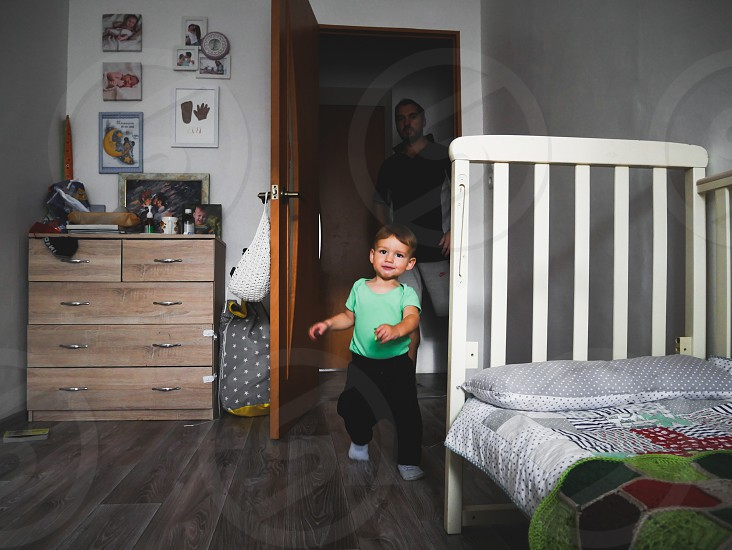 the little boy runs into his children's room. In the shadow of the corridor stands the boy's father photo
