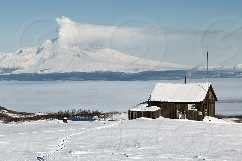 KAMCHATKA PENINSULA RUSSIA - JANUARY 05 2016: Winter view of the field wooden house Kamchatka volcanologists on the background erupting active Shiveluch Volcano. Eurasia Russian Far East Kamchatsky Krai. photo