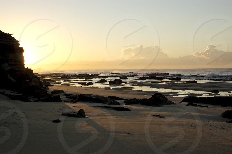 A beautiful sunrise near Cooks Hill NSW Australia. some great puffy clouds rocks tide pools and sun rays. A great way to wake up in the morning.  photo