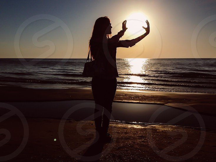 Catching the sun silhouette sea water beach reflection waves sunset photo