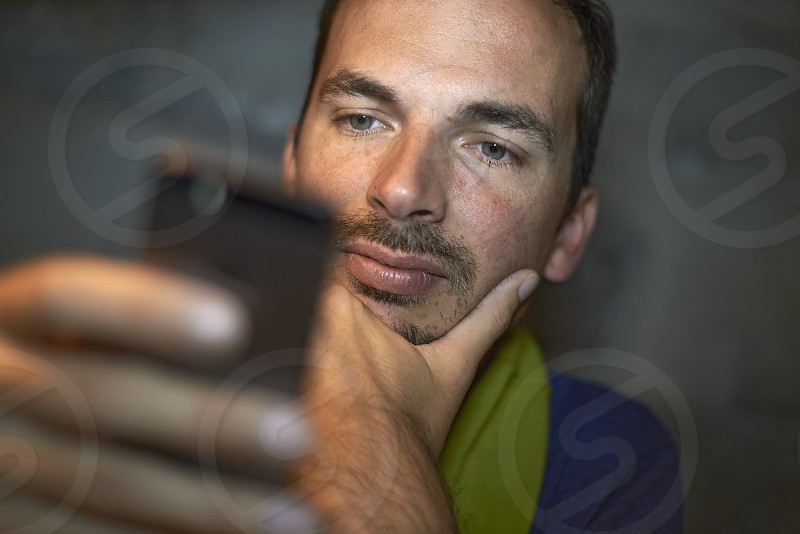 Close up of a caucasian man using his mobile phone texting and calling photo