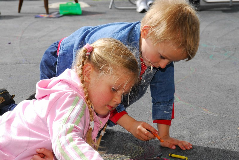 Cute kids little blonde sidewalk chalk drawing playing together happy childhood photo