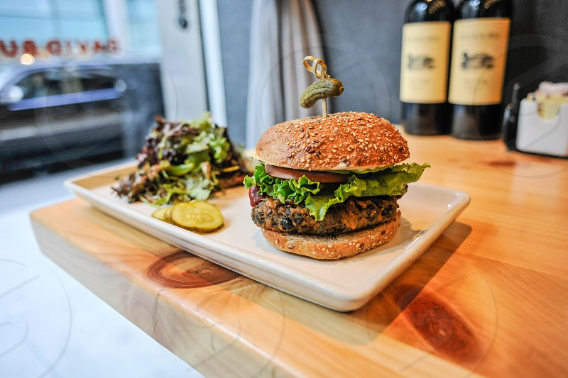 hamburger and pickles on white plate photo
