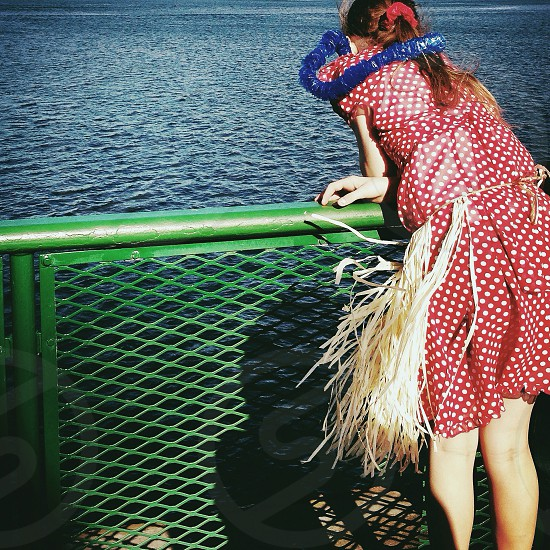 woman in red and white polka dot dress watching at the ocean photo