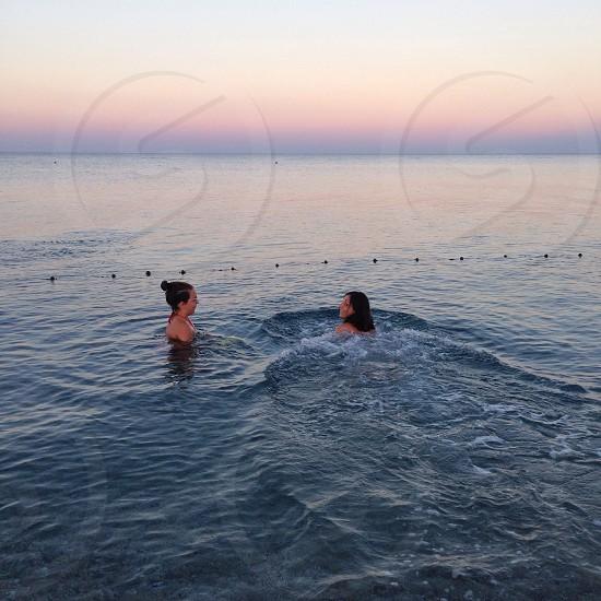 women swimming in blue sea photo