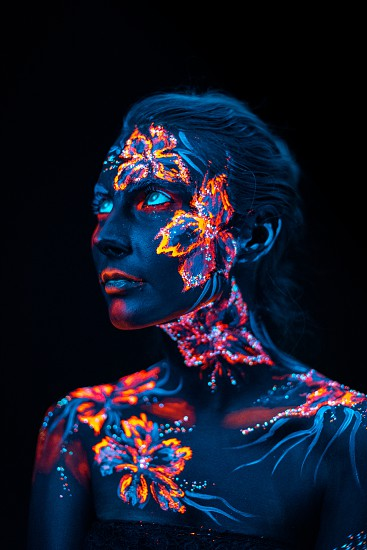 Conceptual face art with shining flowers painted in fluorescent colors isolated on black background photo
