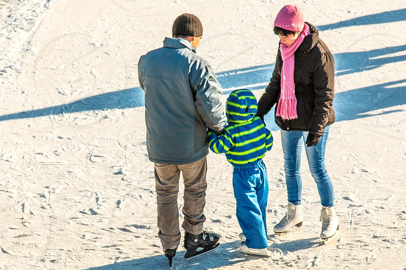 man wearing blue jacket and woman wearing brown jacket assisting a child wearing green jacket on snow field while assisting toddler how to skate during daytime photo