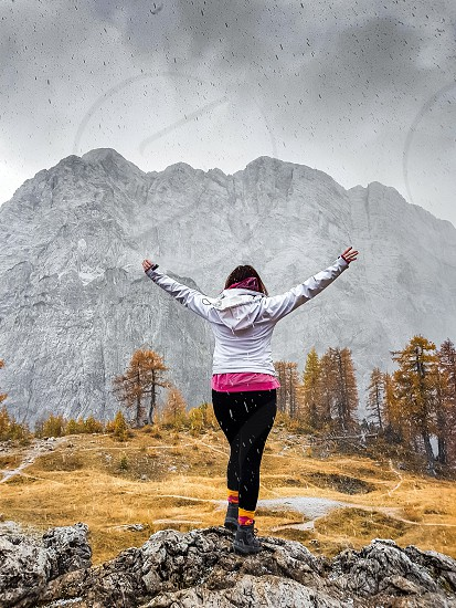 Young woman standing on a rock with her hands raised in the air. Young woman in front of an amazing mountain. photo