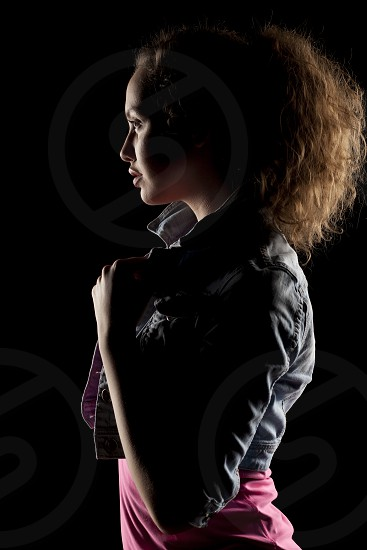 profile of a girl with the face in shadow on a dark background photo