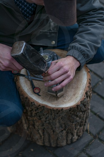 Close up view of male hands working with hammer on a wooden stump photo