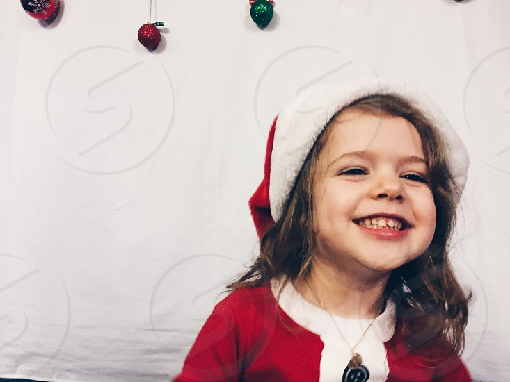 Happy Little girl in Christmas pajamas and Santa hat photo